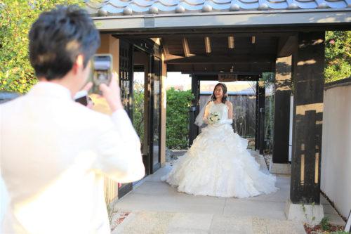 新郎様の撮影に最高の笑顔の新婦様。ウェディングドレスが和空間に映える素敵なフォトに!
